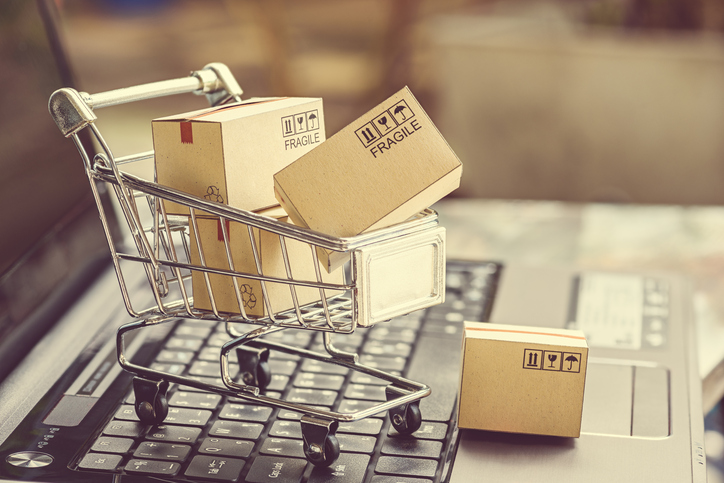 Paper boxes in a shopping cart on a laptop keyboard. Ideas about e-commerce payment processing
