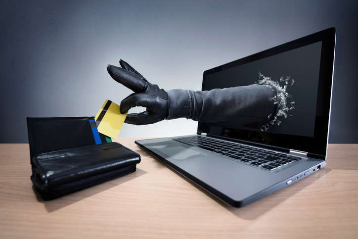 Stealing a credit card through a laptop concept for computer hacker, fraud, network security and electronic banking security