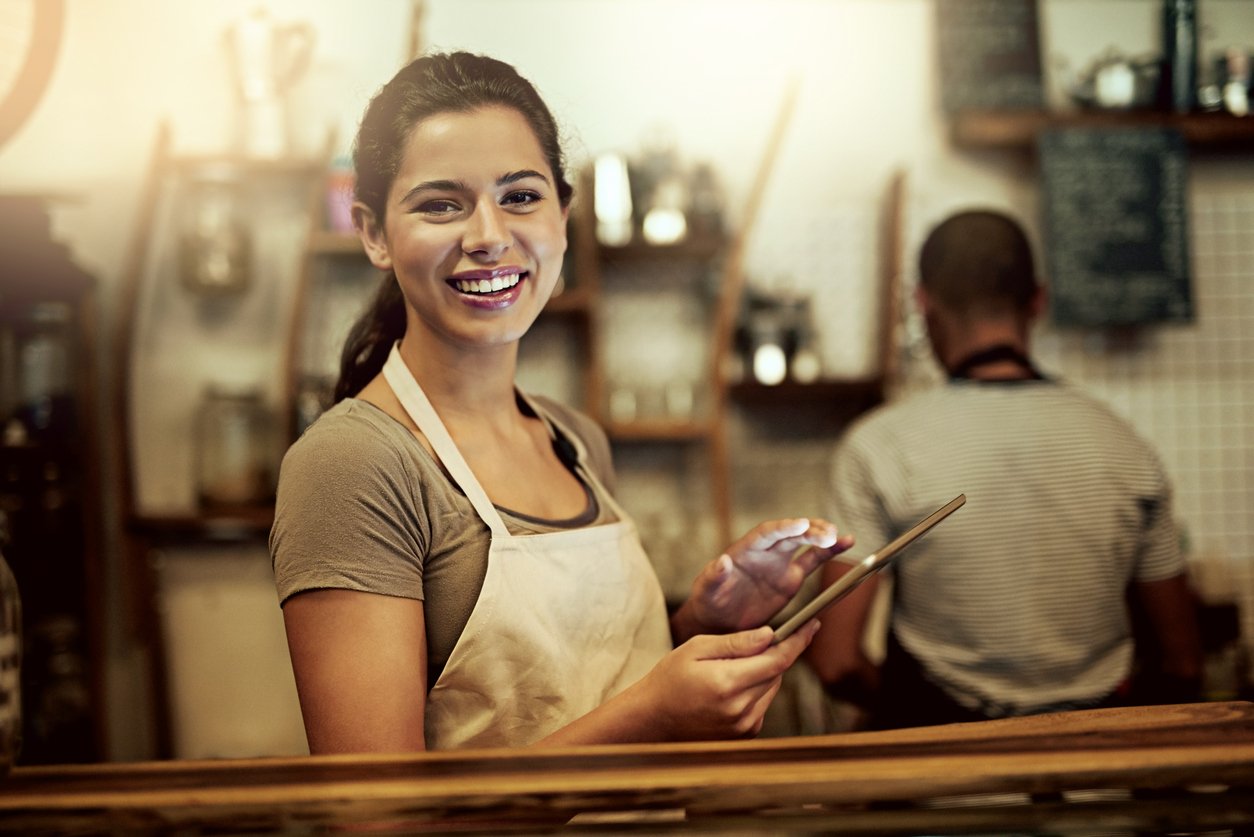 Young woman using a digital tablet with local NYC merchant services while working in a coffee shop